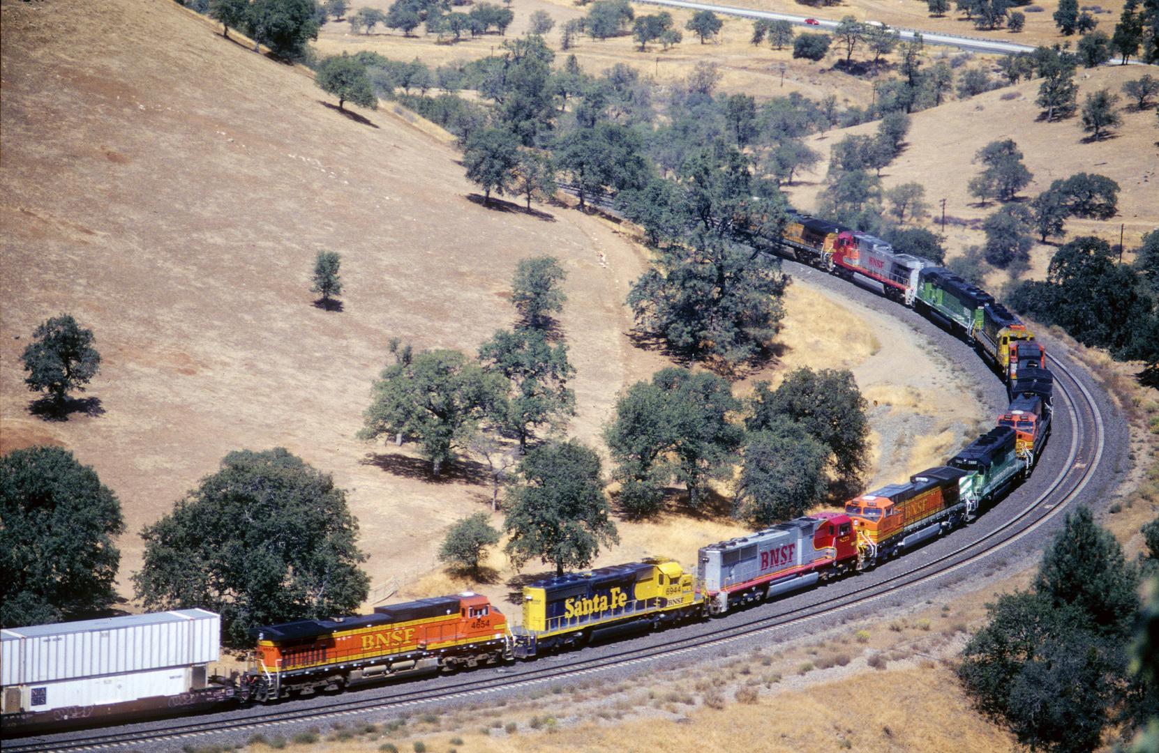 11 Lokomotiven der BNSF ziehen am Tehachapi Loop bergaufwärts einen ca. 2 km langen Güterzug, CA