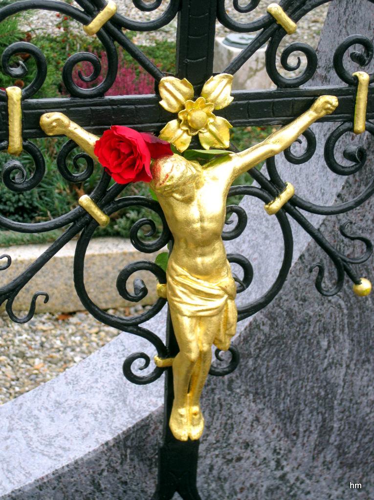 Allerheiligen auf dem Dorffriedhof: Blümchen am Kreuz