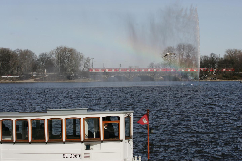 Alsterfontäne mit Regenbogen, Möwe, S-Bahn und Schiff