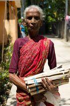 Alte Frau beim Holz holen