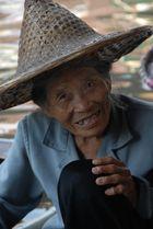 Alte Frau in einem Boot auf den floating markets in Thailand