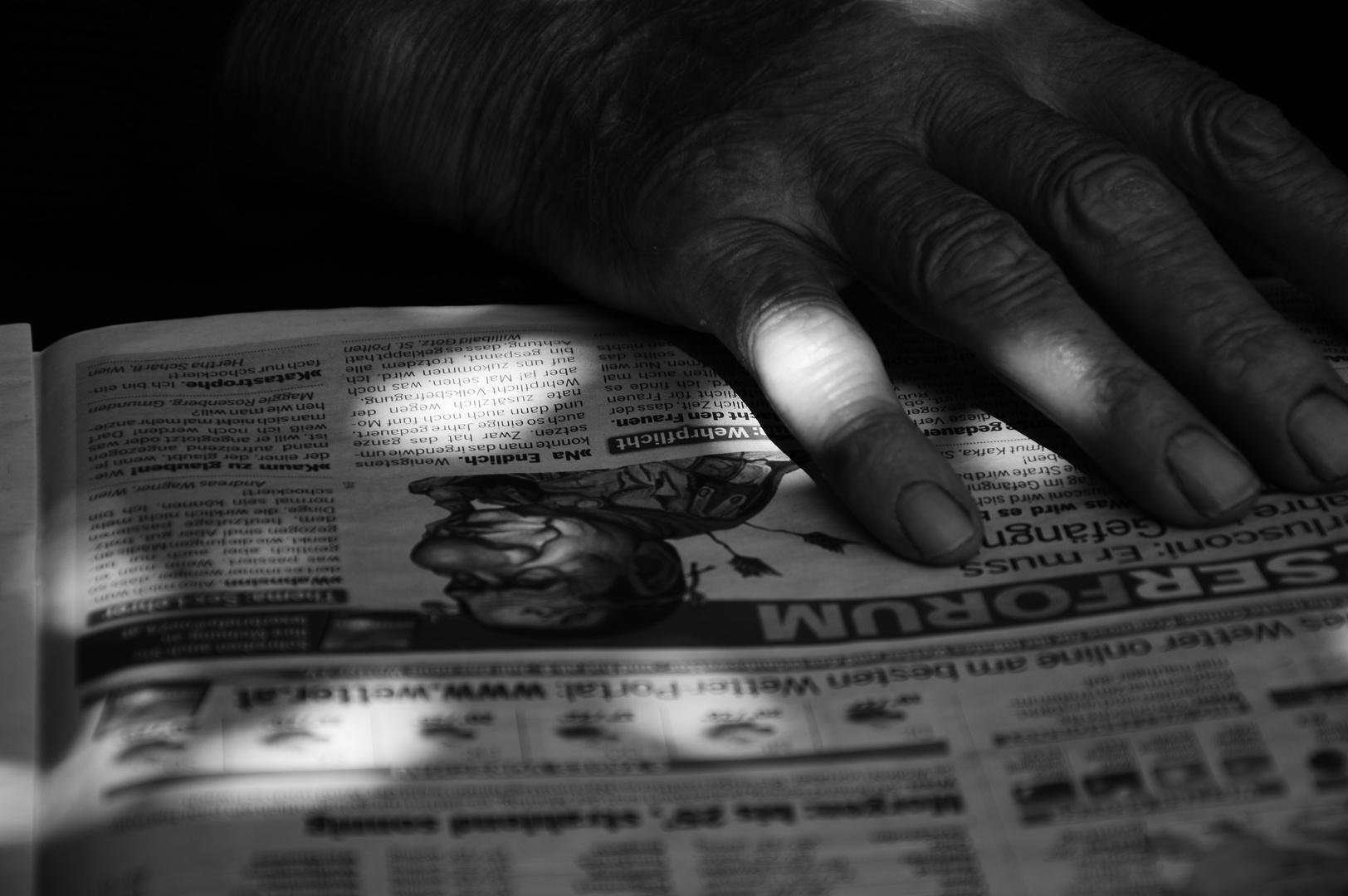 Alte Hand auf Zeitung