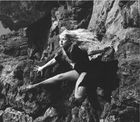 """André de Dienes: """"Model in net stockings posing on rock"""", ca 1950"""