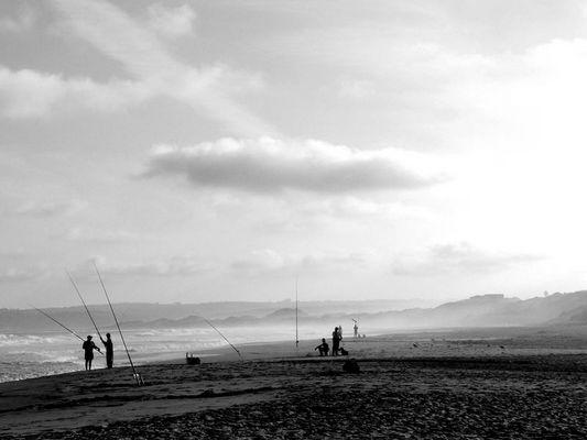 angler am strand in südafrika, in der nähe von knysna