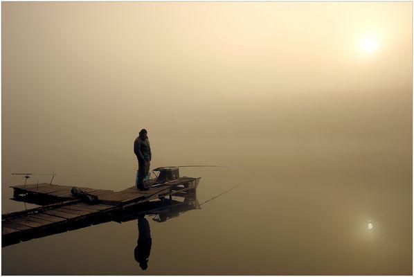 Angler im Nebel bei Sonnenaufgang