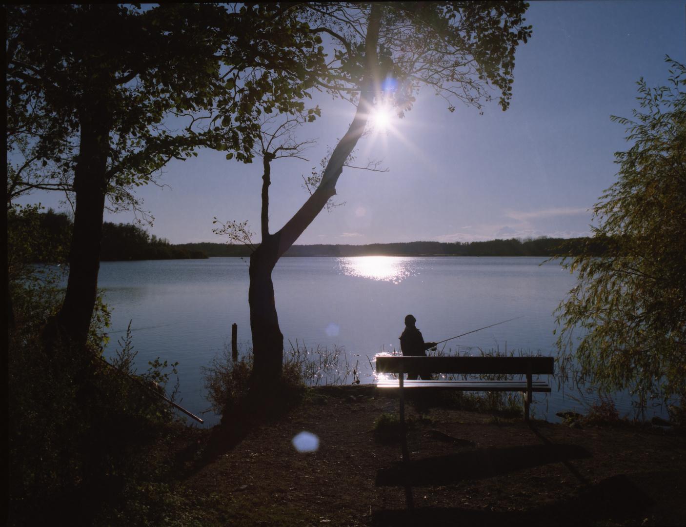 Angler und Bank im Gegenlicht an den Krickenbecker Seen