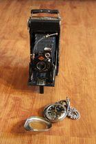 Antike Balgenkamera und die Uhr