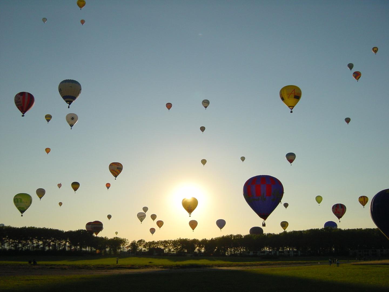 Aufstieg von 48 Heißlutfballons im Gegenlicht