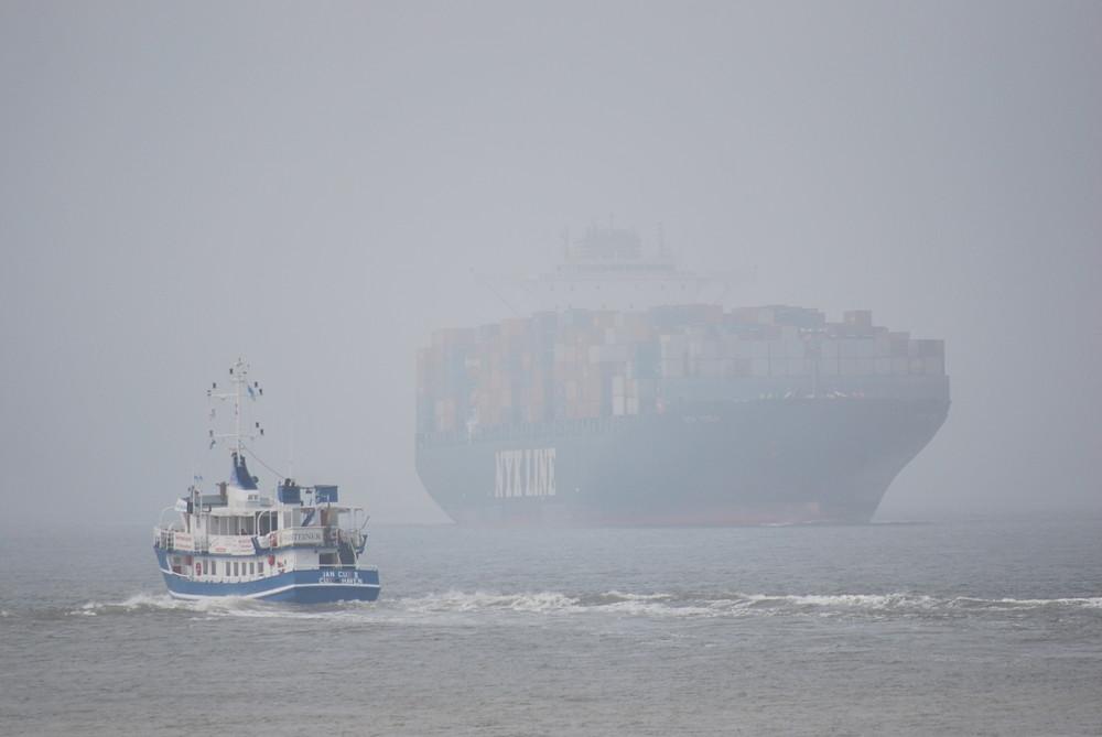 Aus dem Nebel kommt ein Containerschiff