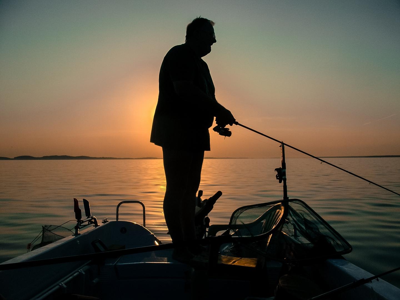 ausdauernder Angler bei Sonnenuntergang