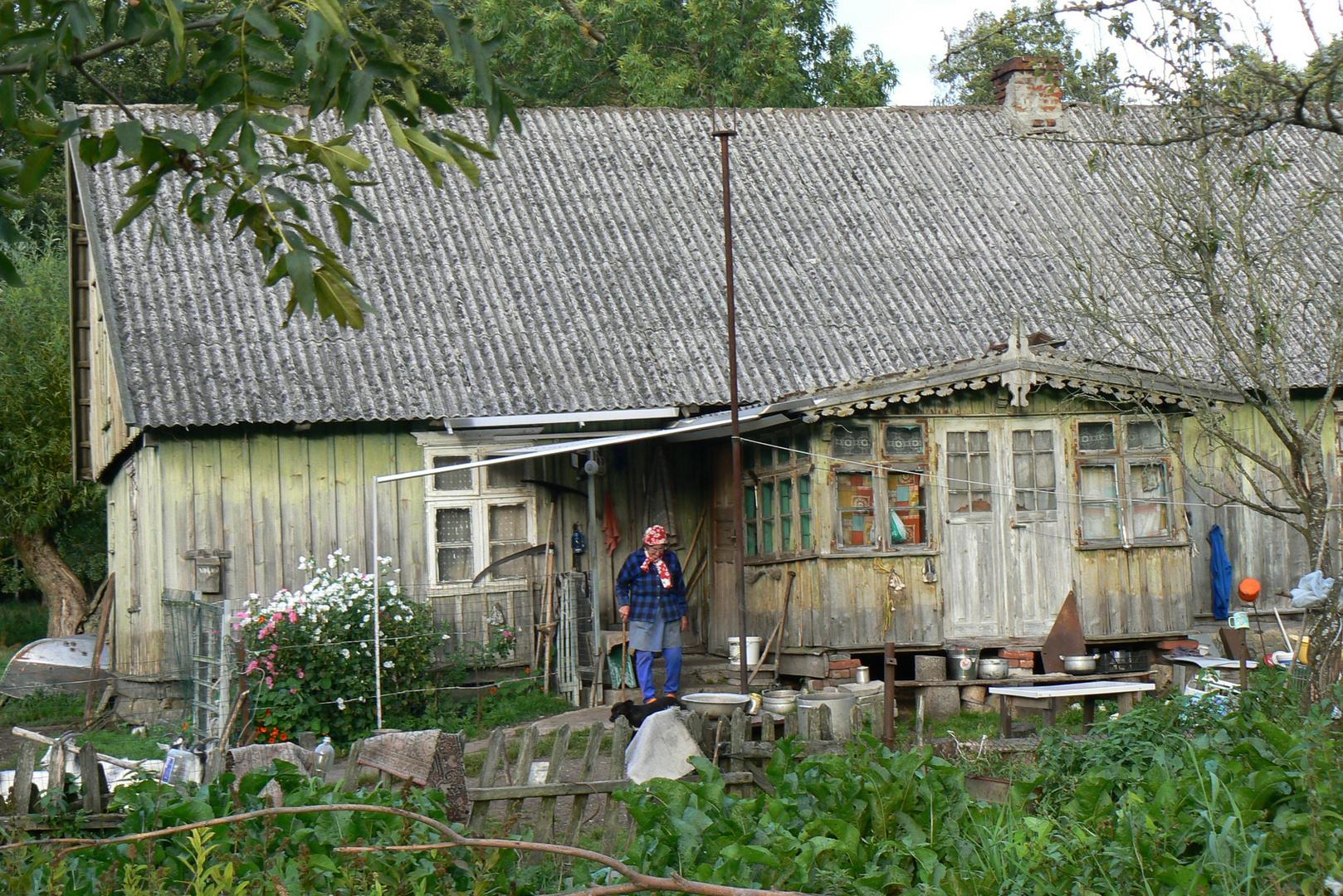 Bäuerin vor ihrem Haus im Memeldelta