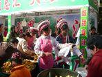 Bai-Maedchen verkaufen Mirabellen auf dem Fruehlingsfestmarkt in Kunming