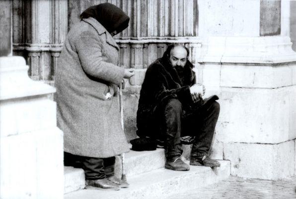 Bettler vor dem Kircheneingang.