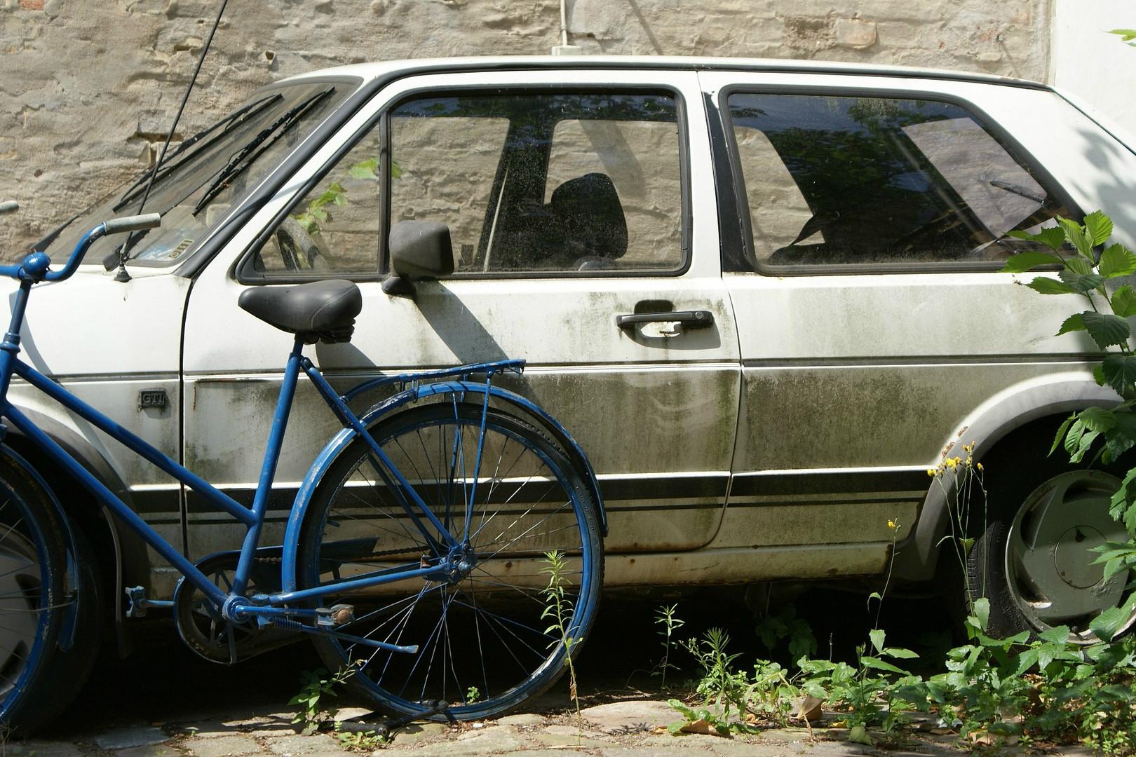 Blå cykel framför vit bil