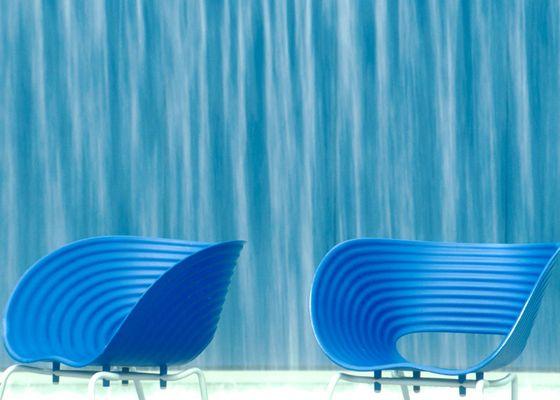 blaue Stühle an der Wasserwand