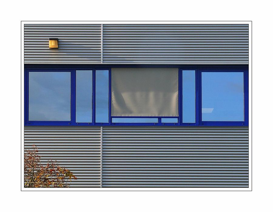 blaues Fenster -häßliche Jalousie-ansprechende Fassade mit Strauch und gelb/orangener Lampe...