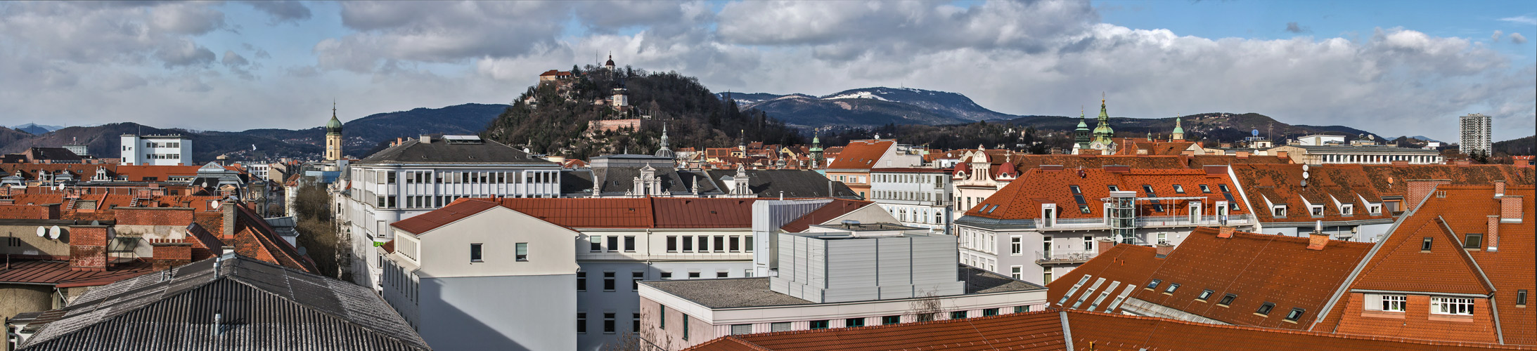 Blick über die Dächer von Graz auf den Schloßberg und den Schöckel am Horizont!