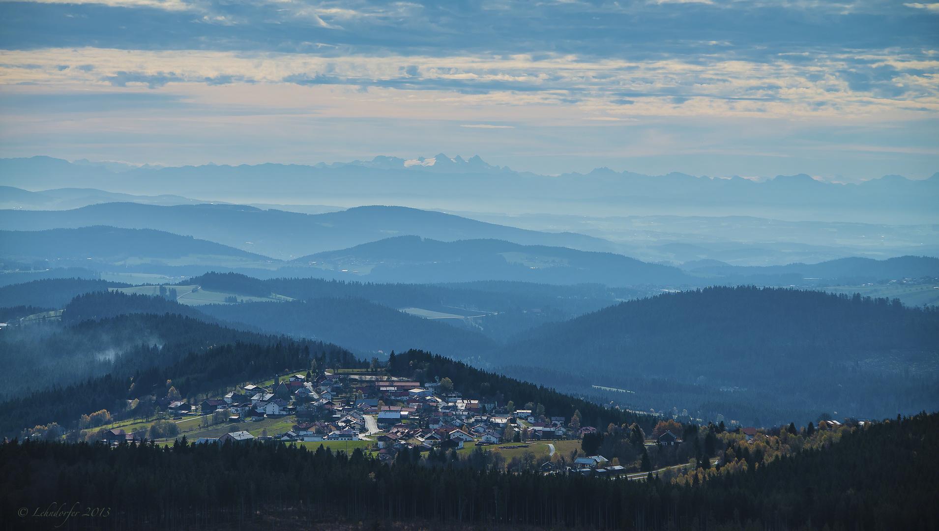 Blick über Finsterau, die Höhenzüge des Bayerischen Waldes bis hin zu den Alpen
