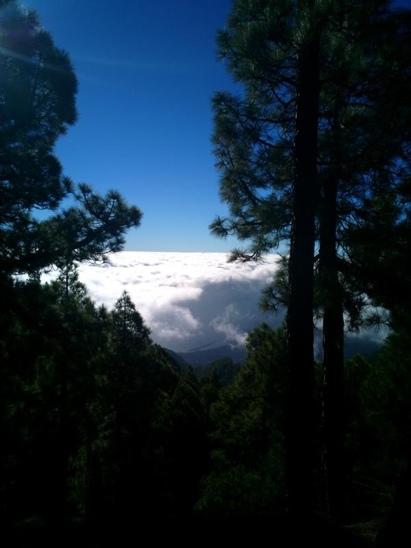Blick vom Vulkan durch die Wolken auf das Meer