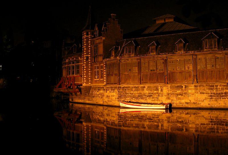 Boot auf nächtlichem Kanal vor antikem Lagerhaus