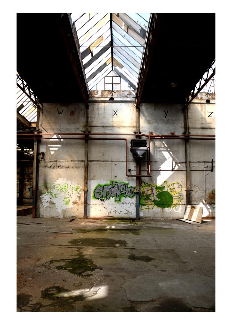 Brach liegende Halle mit Graffiti