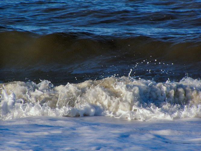 Brechende Welle mit aufspringenden Tropfen