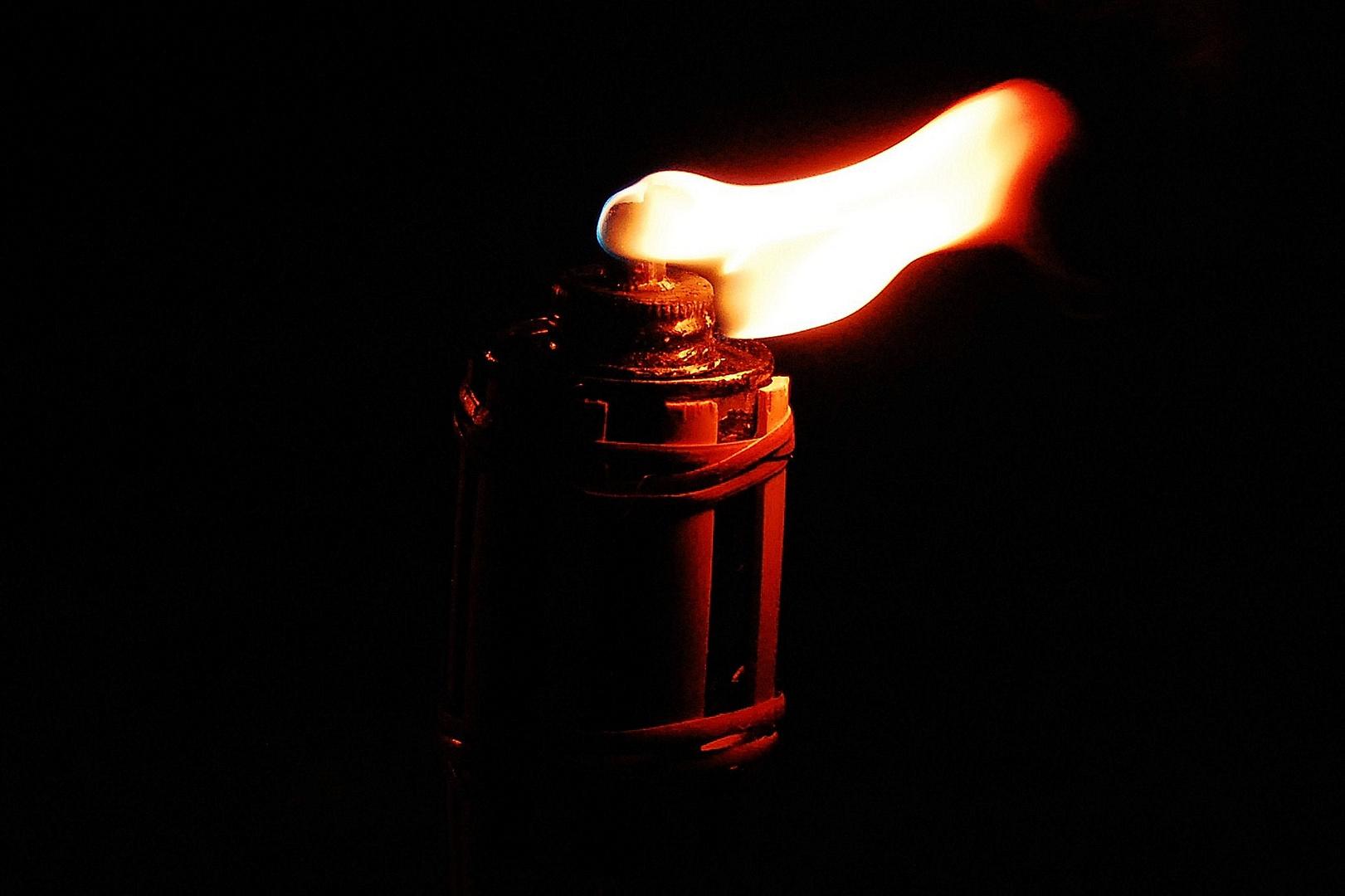 Brennende Fackel im Wind bei Nacht