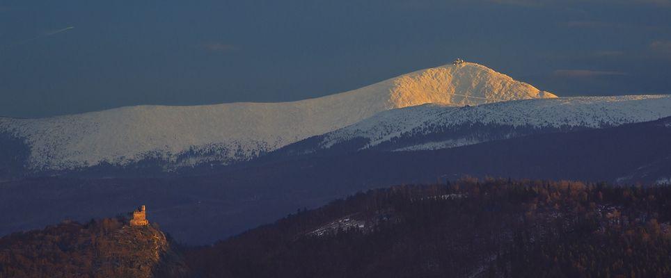 Burg Chojnik und Sniezka im letzten Abendlicht. [Kynast und Schneekoppe]