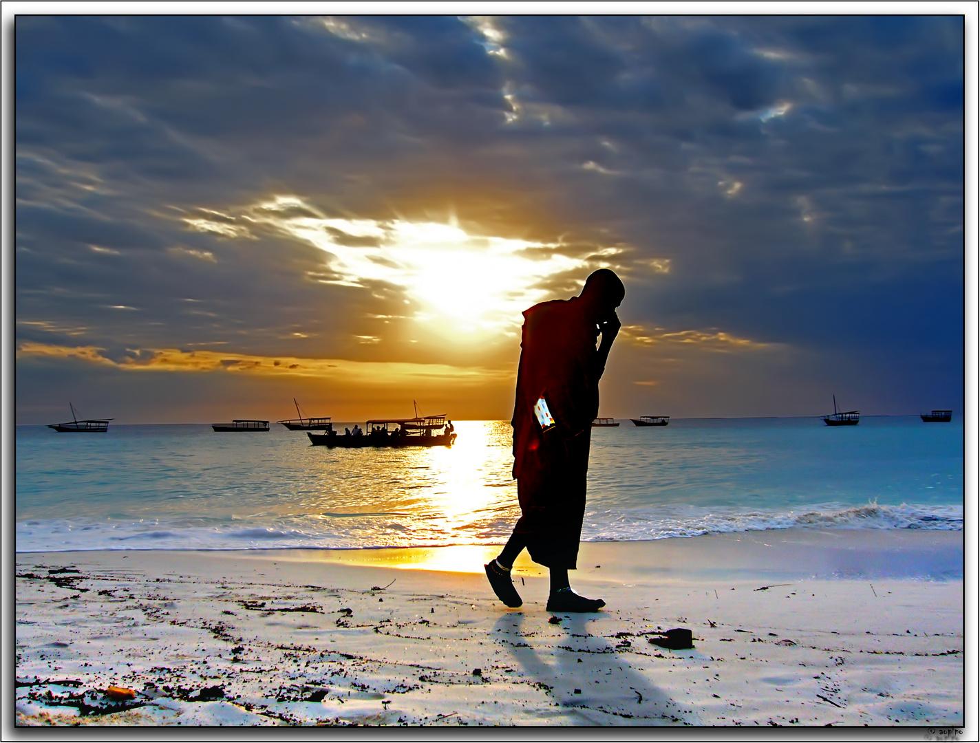 Coversaciones a la puesta del Sol por la playa con el movil (Zanzibar)