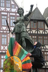 Demo Krise Frankfurt - Mann bringt Fahne an der Brunnenfigur an