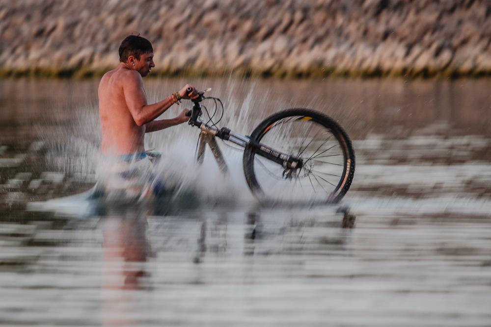 Der Biker der aus dem Wasser kommt