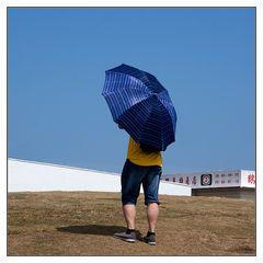 der blaue Schirm am weissen Leuchtturm