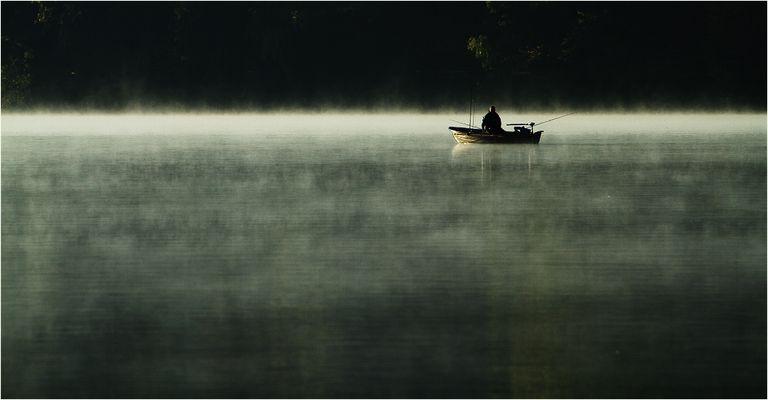 Der frühe Angler fängt den Fisch