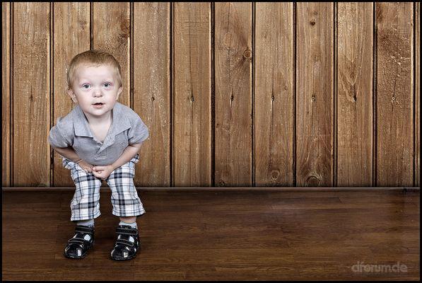 Der Junge vor der Holzwand