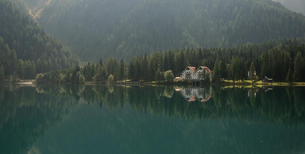 Der Morgennebel am Antholzer See löst sich auf.