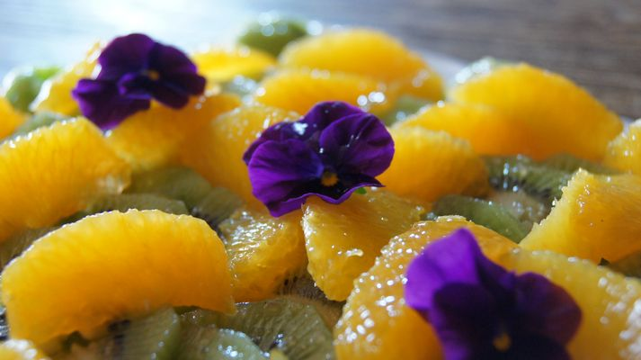 Des couleurs dans l'assiette,Salade de kiwis aux suprêmes d'oranges et fleurs de pensée.