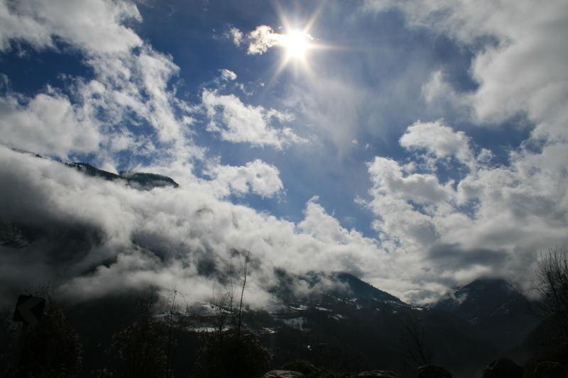 Des nuages en bas de la montagne ensoleillée