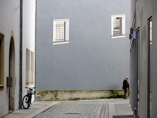 die graue wand, der mann und das fahrrad