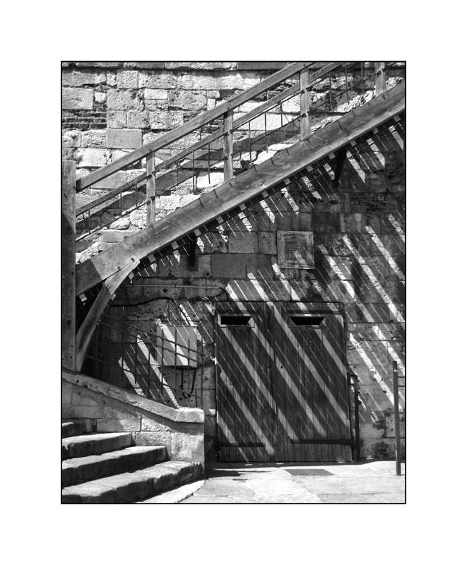 Die Holztreppe, die diagonale Schatten warf