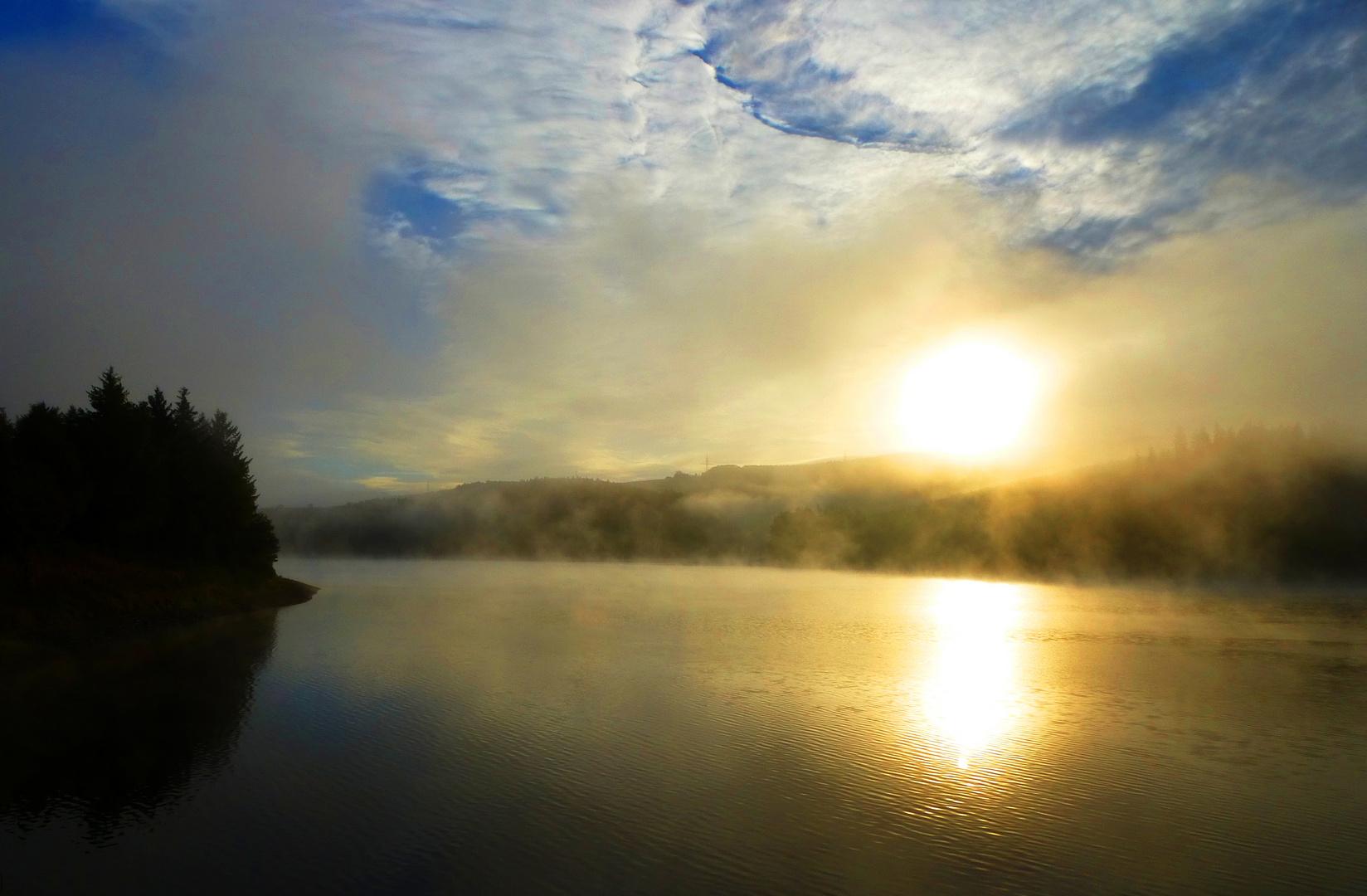 Die Sonne durchbricht den über der Talsperre liegenden zähen Nebel