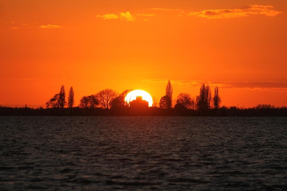 Die Sonne verschwindet hinter der Insel Wilhelmstein.