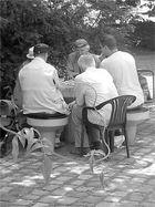 Drei Kiebitze beim Schachspiel