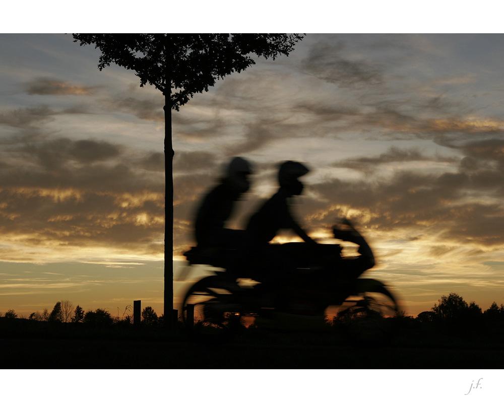eilige Motorradfahrer vor gelassenem Herbsthimmel ...