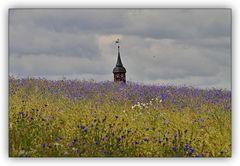 Ein Kirchturm im Feld