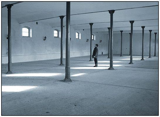 Ein Mann mit Brille und Hut steht in einem Raum mit Säulen und richtet seinen Blick nach oben