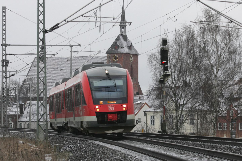 ein roter Zug vor einer Kirche