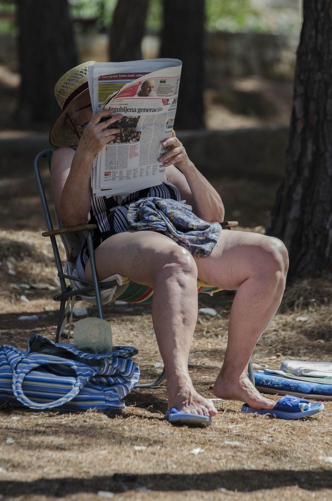 Ein Tag am Strand: Zeitungsleserin