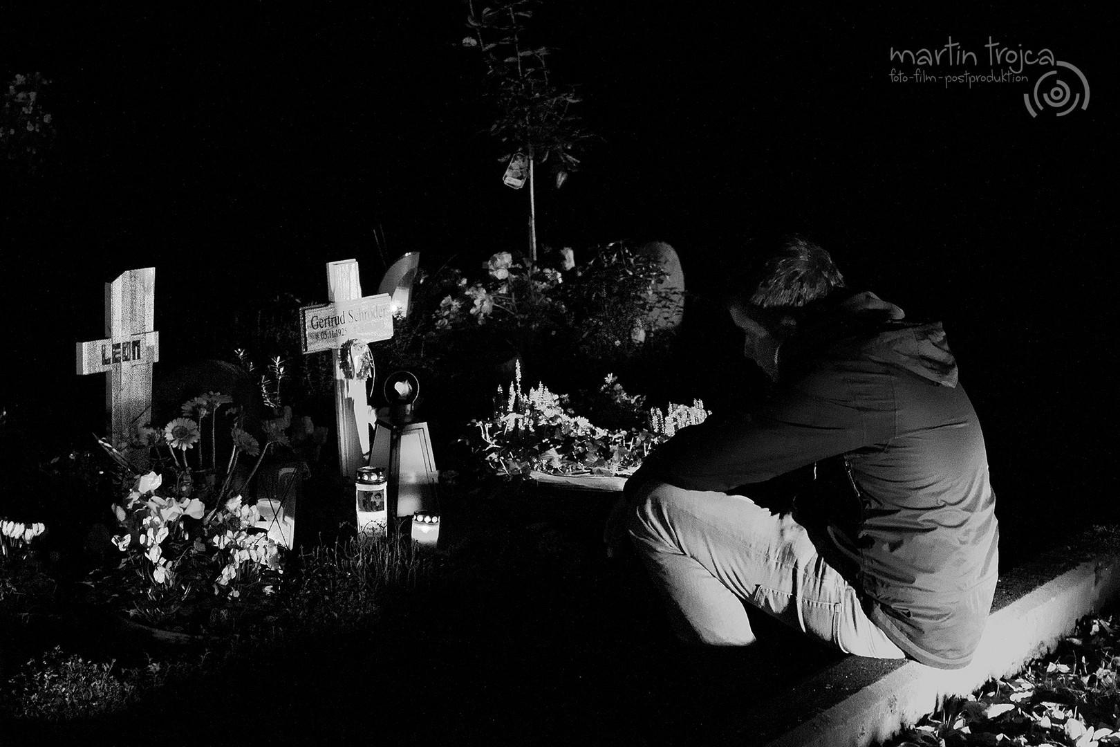 Ein trauernder Junge nachts auf einem Friedhof