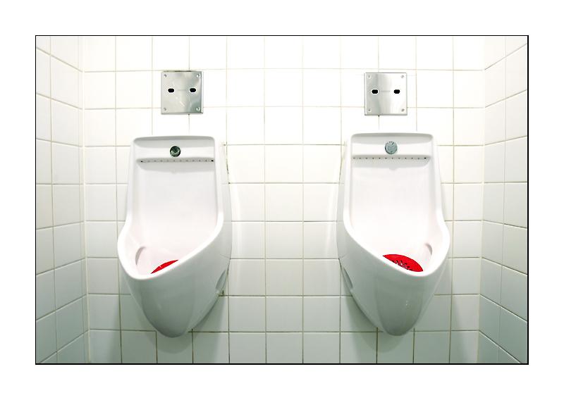 Eine fast weisse Wand mit zwei roten Flecken