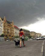 eine frau mit hund geht auf der strasse, es wird gleich regnen